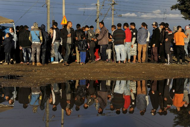 People are reflected in a puddle next to tents following heavy rainfall at a makeshift camp for migrants and refugees at the Greek-Macedonian border near the village of Idomeni, Greece, April 24, 2016. (Photo by Alexandros Avramidis/Reuters)