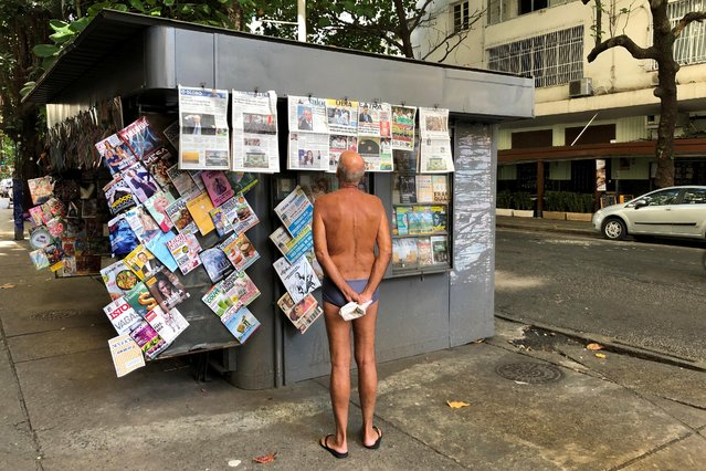 An elderly man reads the morning newspapers at a stand in Ipanema beach in Rio de Janeiro, Brazil on July 24, 2019. (Photo by Jorge Silva/Reuters)