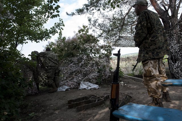 In this photo taken Tuesday, June 23, 2015, Ukrainian servicemen from the Kiev-2 volunteer battalion guard a position at a frontline in the village of Krymske, east Ukraine. (Photo by Evgeniy Maloletka/AP Photo)