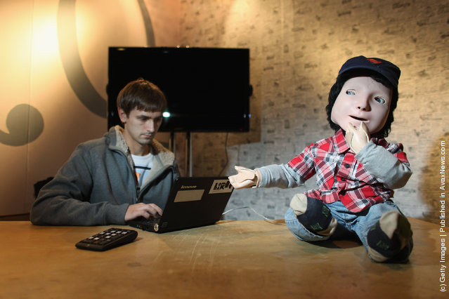 Robotics PhD student Luke Wood works on KASPAR, a robot built at the University of Hertfordshire to help autistic children, in the Robotville exhibition at the Science Museum