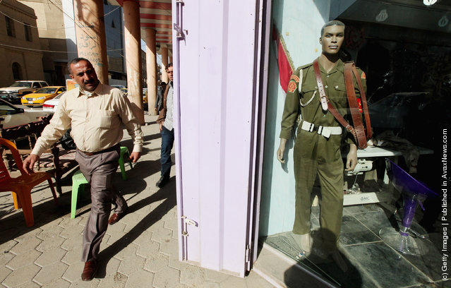 A man walks past a shop that sells uniforms to members of Iraq's military and police forces