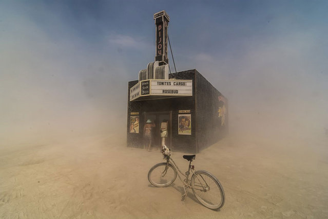 "Finalist, Americana category. Dust swirls around citizens of Black Rock City as they peek into the ""Black Rock Bijou Theatre"", an art installation at the 2013 Burning Man festival. (Photo by Mark Kaplan/Smithsonian.com)"