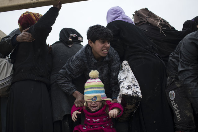 Displaced Iraqis, fleeing fighting between Iraqi security forces and Islamic State militants, are board a truck before being taken to a camp on the western side of Mosul, Iraq, Thursday, March 23, 2017. (Photo by Felipe Dana/AP Photo)