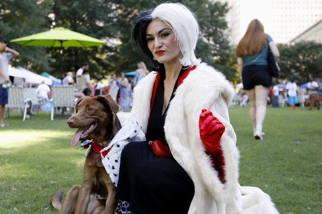 Atlanta-area resident Megan Nelson poses for a photo with her dog Darla during Doggy Con in Woodruff Park, Saturday, August 17, 2019, in Atlanta. Nelson wore a Cruella de Vil costume and dressed her mixed chocolate Labrador Retriever in a Dalmatian outfit. The pair won the costume contest award for best dog and owner combination. (Photo by Andrea Smith/AP Photo)