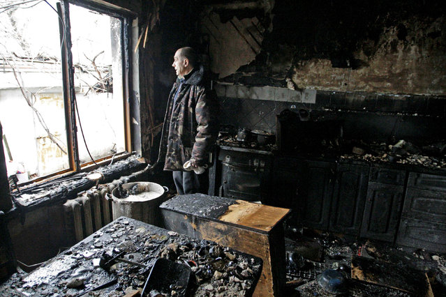 A local resident looks out of a window at his house damaged by shelling, in the rebel-held city of Donetsk, Ukraine March 30, 2017. (Photo by Alexander Ermochenko/Reuters)