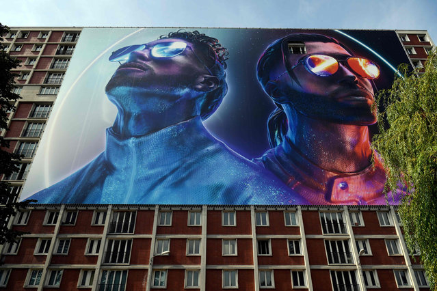 """This picture taken on August 28, 2019 shows a giant banner depicting the two brothers Ademos and N.O.S (Tarik and Nabil Andrieu) of the French rap group PNL (Peace N' Loves), set up on a building where the two artists spent a part of their adolescence, in the Youri Gagarine quarter in Ivry-sur-Seine on the outskirts of the French capital Paris. Some see it as """"the end of a world"""", others """"a page that turns"""": the destruction of the emblematic workers' quarter Gagarine, at the gates of Paris, emblem of the red suburbs, arouses the nostalgia and apprehension of residents who attend the entrance of their city in the era of Greater Paris. Inaugurated in 1963 in the presence of Russian space pioneer Yuri Gagarin – just two years after he became the first person in space – the """"Cite Gagarine"""" underscored the Communist Party's appeal in much of postwar France. (Photo by Lionel Bonaventure/AFP Photo)"""