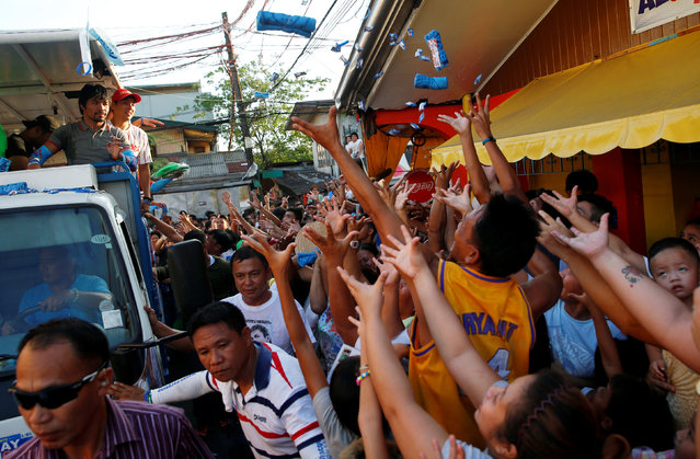 Supporters jostle for election souvenirs thrown by Filipino boxer and Senatorial candidate Manny Pacquiao during election campaigning in Malabon Metro Manila in the Philippines May 6, 2016. (Photo by Erik De Castro/Reuters)
