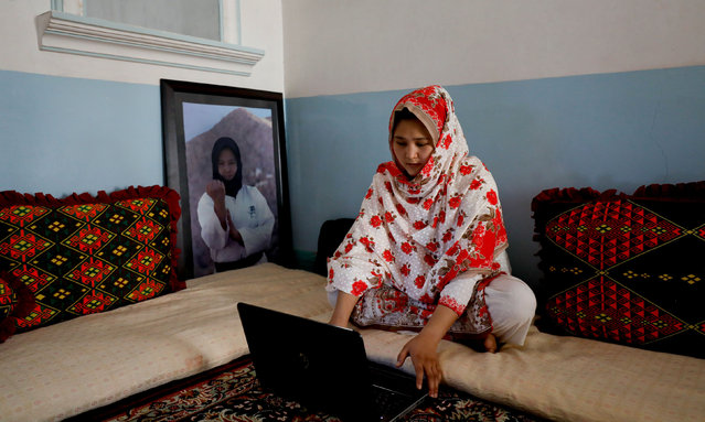 "Nargis Hazara, 20, martial arts specialist, who belongs to ethnic Hazara community, works on her computer as she sits beside her portrait at her home in Hazara Town, Quetta, Pakistan, June 13, 2019. Domestic media often portray the Hazaras as targets of sectarian attacks or holding sit-ins to demand greater protection, but the community is developing and growing, said Nargis, who last year became Pakistan's first winner of an Asian Games medal in karate. ""Every one of us has a dream, a target and aim in our heart, to change the image of Hazaras in the world, and especially in Pakistan"". (Photo by Akhtar Soomro/Reuters)"