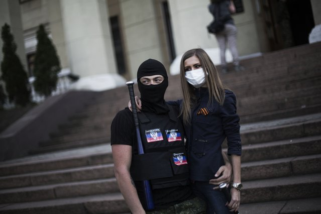 Masked pro-Russia militants stand outside a local television broadcasting center after storming it in Donetsk, Ukraine, Sunday, April 27, 2014. A crowd of hundreds of pro-Russia activists stormed the television broadcasting center in Donetsk, the regional capital of eastern Ukraine, to demand that Russian state channels be put back on the air. The Kiev government last month blocked the broadcasts of the Russian channels, which serve as propaganda tools for the Kremlin. (Photo by Manu Brabo/AP Photo)