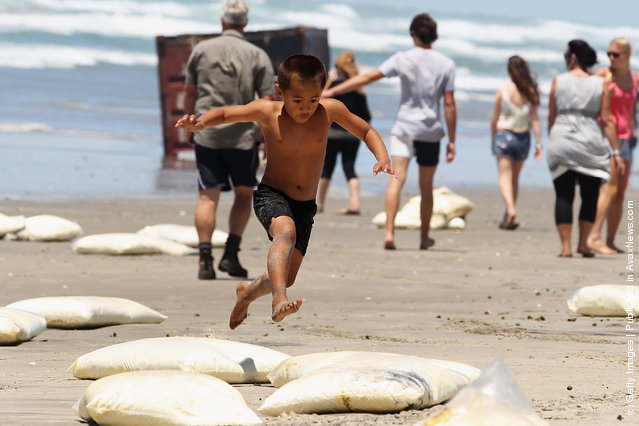 A boy jumps over washed up bags of milk powder at Waihi Beach
