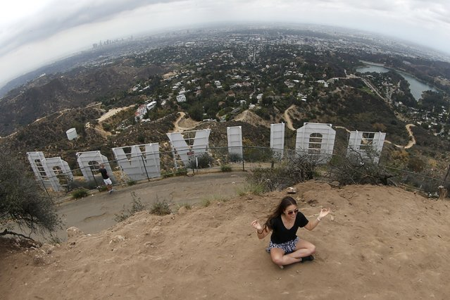 A woman strikes a yoga pose for a friend's photo behind the Hollywood sign in Los Angeles, California, United States July 9, 2015. Hollywood Hills residents sued the city last week, according to local media. They demanded the closure of a popular Hollywood sign viewing path, until effects the crowds have on the neighborhood is assessed. (Photo by Lucy Nicholson/Reuters)