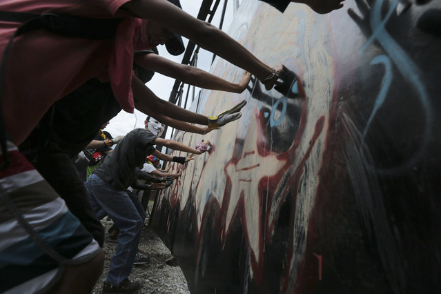 Ant-Government protesters tear down an iron gate in Caracas, Venezuela, Wednesday, April 19, 2017. (Photo by Fernando Llano/AP Photo)