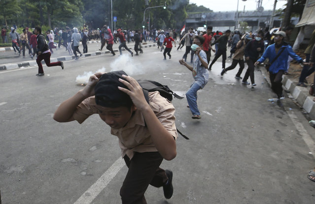 Student protesters run from tear gas fired by police officers during a protest in Jakarta, Indonesia Wednesday, September 25, 2019. Indonesian riot police shot multiple rounds of tear gas at thousands of stone-throwing students who attempted to reach Parliament in Jakarta on Wednesday to protest a new law that critics say cripples the country's anti-corruption agency. (Photo by Achmad Ibrahim/AP Photo)