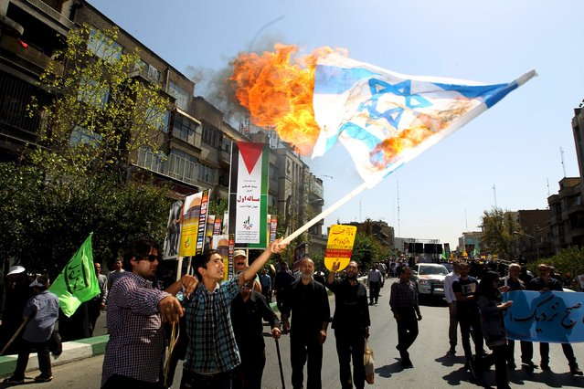 Iranian demonstrators burn an Israeli flag during a rally marking al-Quds (Jerusalem) Day in Tehran July 10, 2015. (Photo by Reuters/Stringer/TIMA)