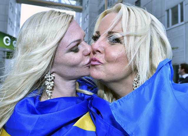 Eurovision fans from Sweden kiss in front of the Globen Arena prior the first the Eurovision Song Contest final in Stockholm, Sweden, Saturday, May 14, 2016. (Photo by Martin Meissner/AP Photo)
