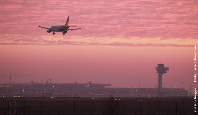 A passenger plane lands at Schoenefeld Aiport next to the construction site and the new control tower of the new Berlin Brandenburg International Aiport (BBI) at sunrise