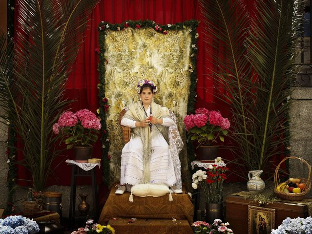 """In this photo taken on Sunday, May 11, 2014 a """"Maya"""" girl sits on an altar during the traditional celebration of """"Las Mayas"""" on a street, in central Madrid, Spain. (Photo by Daniel Ochoa de Olza/AP Photo)"""