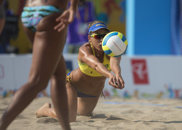 Brazil's Liliane Maestrini dives for a ball in Brazil's beach volleyball preliminary match against Nicaragua, at the Pan Am Games in Toronto, Monday, July 13, 2015. (Photo by Rebecca Blackwell/AP Photo)