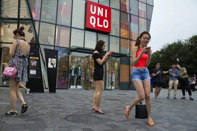 Chinese women take photos outside the Uniqlo flagship store where a steamy video purportedly taken inside one of its fitting room showing a couple apparently having s*x in Beijing, Thursday, July 16, 2015. (Photo by Ng Han Guan/AP Photo)