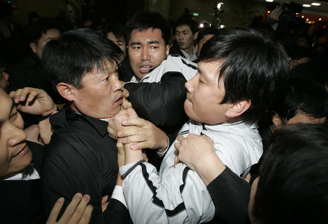Members (R) of the opposition parties scuffle with parliament security guards at the National Assembly in Seoul, January 3, 2009. (Photo by Jo Yong-Hak/Reuters)
