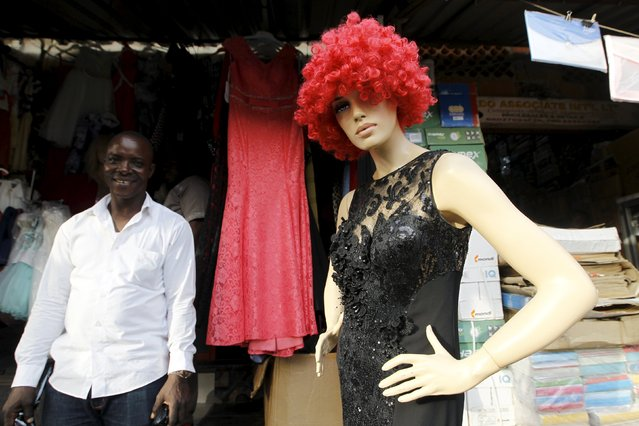 A man stands by a dressed mannequin on the eve of Christmas at Wuse market in Abuja, Nigeria December 24, 2015. (Photo by Afolabi Sotunde/Reuters)