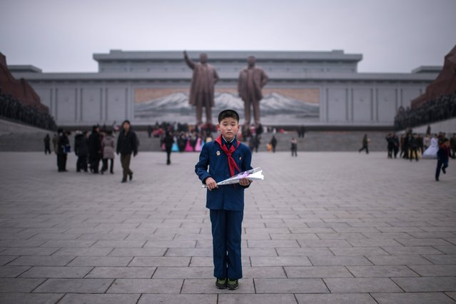 "In this photo taken on February 16, 2017, Kim Su-Min, 11, poses for a portrait before offering flowers to the statues of late North Korean leaders Kim Il-Sung (top L) and Kim Jong-Il (top R) at Mansudae hill in Pyongyang. Kim Su-Min was observing the anniversary of the birth of late North Korean leader Kim Jong-il, a public holiday known as the ""Day of the Shining Star"", during which residents of Pyongyang leave flowers at the feet of the statue. (Photo by Ed Jones/AFP Photo)"