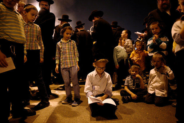An Ultra-Orthodox Jewish boy prays by a bonfire as he celebrates the Jewish holiday of Lag Ba'Omer in the city of Ashdod, Israel May 25, 2016. (Photo by Amir Cohen/Reuters)