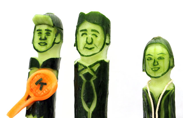 Cucumbers carved by Japanese sushi chef Okitsugu Kado with the faces of (L-R) tennis player Kei Nishikori, Prime Minister Shinzo Abe and figure skater Mao Asada are displayed during a promotional event in Tokyo on July 22, 2015. Japan's Tohoku region's farmers held the event to  promote their cucumbers as a good food for rehydration on hot summer days. (Photo by Yoshikazu Tsuno/AFP Photo)