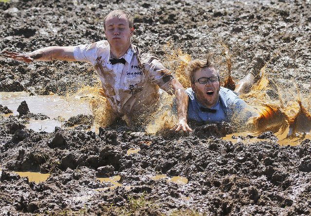 Players celebrate winning a match during the German Mud Soccer  Championships in Rieste, Germany, Saturday, May 31, 2014. Some 1,000 participants from all over Germany compete in three categories, men, women and mixed for the German Championship titles.  (Photo by Frank Augstein/AP Photo)