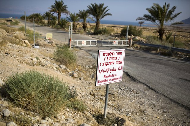 A sign warning of sinkholes is seen at the entrance to an abandoned tourist resort on the shore of the Dead Sea, Israel July 27, 2015. (Photo by Amir Cohen/Reuters)