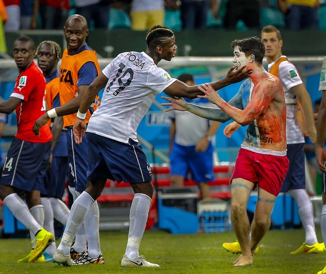 France's Paul Pogba attempts to hold a fan who ran onto the field after the group E World Cup soccer match between Switzerland and France at the Arena Fonte Nova in Salvador, Brazil. The match ended in a 5-2 win for France. (Photo by David Vincent/Associated Press)