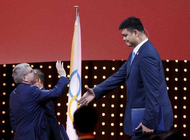 President of the International Olympic Committee (IOC) Thomas Bach waves to China's Olympic basketball player Yao Ming as he arrives for Beijing's 2022 Winter Games presentation at the 128th International Olympic Committee Session in Kuala Lumpur, Malaysia, July 31, 2015. (Photo by Olivia Harris/Reuters)