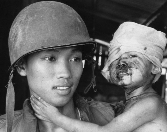 A South Vietnamese soldier holds a wounded boy who is the only surviving member of his family after North Vietnamese opened fired on a group of refugees fleeing south from An Loc along Route 13 on June 22, 1972. (Photo by AP Photo)