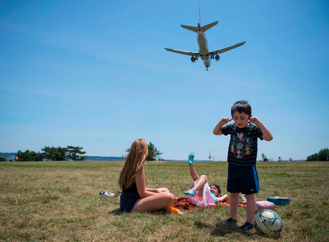 A young boy plugs his ears as his sister (C) and nanny (L) watch from Gravelly Point Park as planes land at Reagan National Airport in Arlington, Virginia on June 29, 2017. President Donald Trump' s travel ban on people from six mostly Muslim countries will come into force late Thursday, as controversy swirls over who qualifies for an exemption based on family ties. (Photo by Jim Watson/AFP Photo)