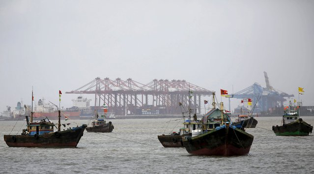 Fishing trawlers are seen in front of the Jawaharlal Nehru Port Trust (JNPT) in Mumbai, India, July 31, 2015. Mumbai's commercial seaport, which handles over half the container traffic through India's major ports, is doubling capacity as Prime Minister Narendra Modi seeks to build an export powerhouse. (Photo by Shailesh Andrade/Reuters)