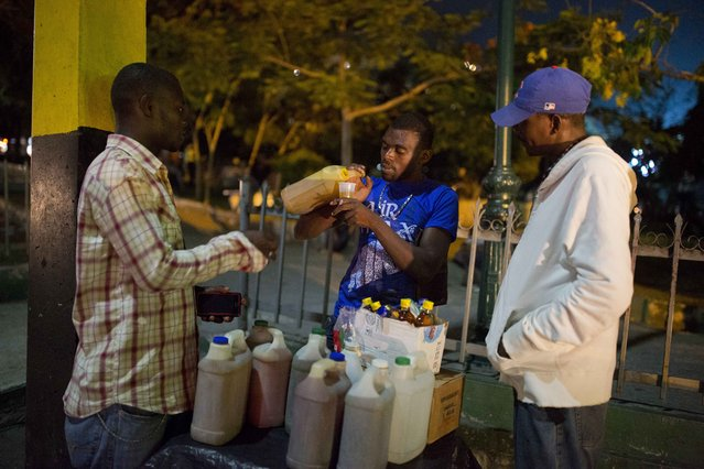 In this June 23, 2017 photo, Smith Nazon, 29, sells clairin, a sugar-based alcoholic drink, on the sidewalk in Petion-Ville, Haiti. A 1 liter bottle sells for about $1.36 dollars, about one-eighth the price of the least expensive bottle of Barbancourt rum, Haiti's most famous export. (Photo by Dieu Nalio Chery/AP Photo)
