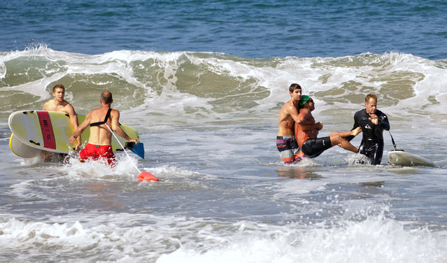 Two men carry a swimmer, second from right, after he was bitten by a great white shark, as lifeguards close in at left in the ocean off Southern California's Manhattan Beach, Saturday, July 5, 2014. The man, who was with a group of long-distance swimmers when he swam into a fishing line, was bitten on a side of his rib cage according to Rick Flores, a Los Angeles County Fire Department spokesman. The man's injuries were not life-threatening and he was taken to a hospital conscious and breathing on his own, Flores said. (Photo by Laura Joyce/AP Photo)