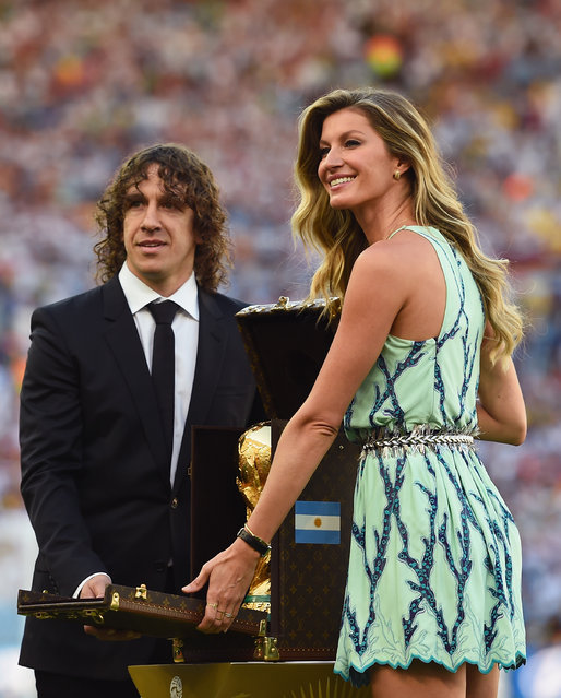 Former Spanish international Carles Puyol and model Gisele Bundchen present the World Cup trophy in a Louis Vuitton case prior to the 2014 FIFA World Cup Brazil Final match between Germany and Argentina at Maracana on July 13, 2014 in Rio de Janeiro, Brazil.  (Photo by Laurence Griffiths/Getty Images)