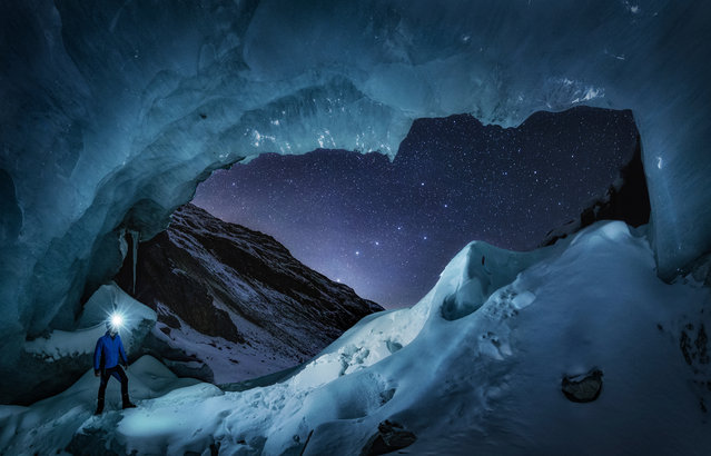 """Mr Big Dipper"", Nicholas Roemmelt (Denmark). A stargazer observes the constellation of the Big Dipper perfectly aligned with the window of the entrance to a large glacier cave in Engadin, Switzerland. This is a panorama of two pictures, and each is a stack of another two pictures: one for the stars and another one for the foreground, but with no composing or time blending. (Photo by Nicholas Roemmelt/National Maritime Museum/The Guardian)"