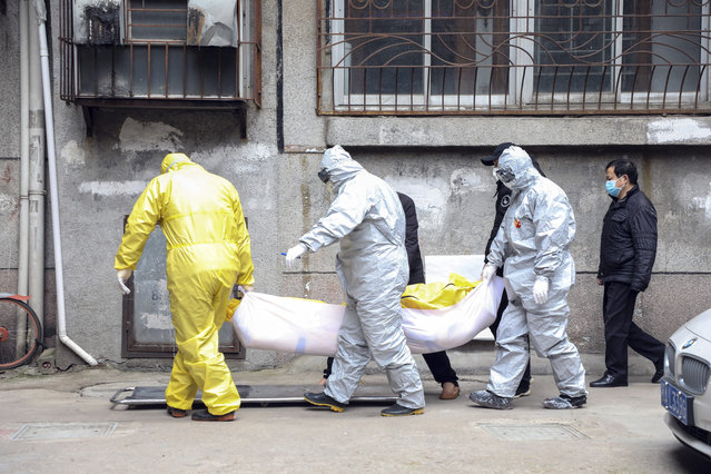 In this February 1, 2020, photo, funeral home workers remove the body of a person suspect to have died from a virus outbreak from a residential building in Wuhan in central China's Hubei Province. The Philippines on Sunday reported the first death from a new virus outside of China, where authorities delayed the opening of schools in the worst-hit province and tightened quarantine measures in a city that allow only one family member to venture out to buy supplies. (Photo by Chinatopix via AP Photo)