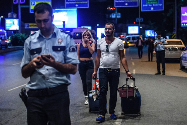 People leave the airport after two explosions followed by gunfire hit the Turkey's biggest airport of Ataturk in Istanbul, on June 28, 2016. At least 10 people were killed on June 28, 2016 evening in a suicide attack at the international terminal of Istanbul's Ataturk airport, Turkish Justice Minister Bekir Bozdag said. Turkey has been hit by a string of deadly attacks in the past year, blamed on both Kurdish rebels and the Islamic State jihadist group. (Photo by Ozan Kose/AFP Photo)