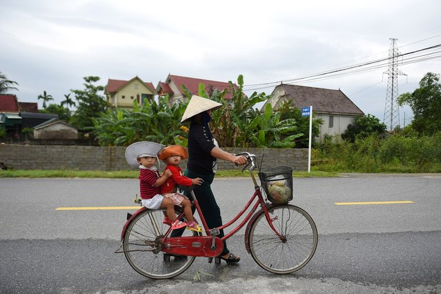 "A woman carries children on a bicycle in Nghe An province where families of missing Vietnamese migrants reside on October 29, 2019. For up to $50,000, Vietnamese migrants can get the ""VIP package"" to Britain – flight, fake passport and even a lawyer – illegal, but billed as safer than cheaper overland routes by people smugglers who provide a menu of options for those trying to reach the UK. (Photo by Nhac Nguyen/AFP Photo)"