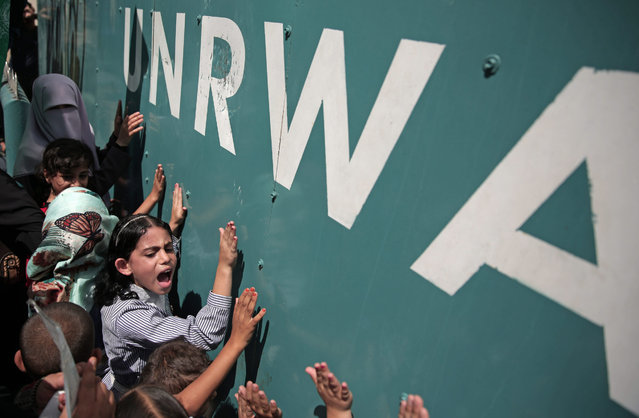 "A Palestinian school girl chants slogans during a demonstration against a U.N. Relief and Works Agency (UNRWA) funding gap that could about keep 500,000 Palestinian students out of school this fall, outside the UNRWA Gaza Headquarters in Gaza City, Sunday, August 16, 2015. The deputy chief of the UNRWA, which operates 700 schools, Sandra Mitchell, said that ""if funding does not arrive"" this month, the agency could delay the start of the school year. (Photo by Khalil Hamra/AP Photo)"