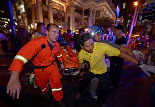 Thai rescue workers carry an injured person after a bomb exploded outside a religious shrine in central Bangkok late on August 17, 2015 killing at least 10 people and wounding scores more.  Body parts were scattered across the street after the explosion outside the Erawan Shrine in the downtown Chidlom district of the Thai capital. (Photo by Pornchai Kittiwongsakul/AFP Photo)