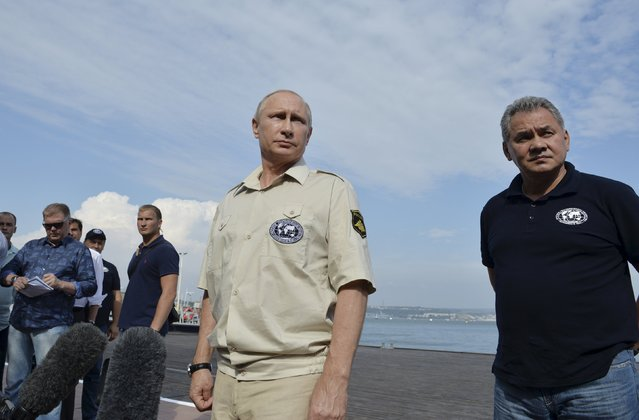 Russian President Vladimir Putin (C), accompanied by Defence Minister and President of the Russian Geographical Society Sergei Shoigu (R), meets with journalists after submerging into the waters of the Black Sea inside a research bathyscaphe as part of an expedition in Sevastopol, Crimea, August 18, 2015. (Photo by Alexei Druzhinin/Reuters/RIA Novosti/Kremlin)