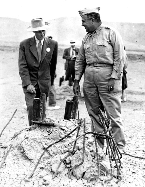 """This September 9, 1945, file photo Gen. Leslie R. Groves, right, and Dr. J. Robert Oppenheimer, who cooperated on the development of the atomic bomb, survey the area in Alamogordo, N.M., where a tower once stood before the test bomb exploded. A new PBS special looks into the creation of the atomic bomb in the city of Los Alamos and will feature newly-restored footage of nuclear weaponry. """"The Bomb"""", which begins airing Tuesday, July 28, 2015, on most PBS stations, seeks to tell the story of the deadly device as the 70th anniversary of the atomic bombings of Hiroshima and Nagasaki approaches. (Photo by AP Photo)"""