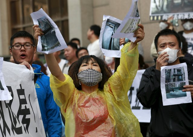 A resident evacuated from her home after last week's explosions in Binhai new district, shouts slogans while holding images of her damaged house during a rally outside the venue of a government officials' news conference in Tianjin, China, August 19, 2015. Around 150 homeowners whose estate was destroyed in the Tianjin explosions protested to demand government action on Wednesday. (Photo by Kim Kyung-Hoon/Reuters)