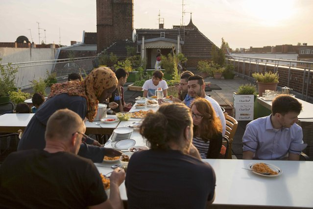 """Migrants and Germans of the """"Sharehaus Refugio"""" community have dinner on their roof garden in Berlin, Germany August 19, 2015. (Photo by Axel Schmidt/Reuters)"""