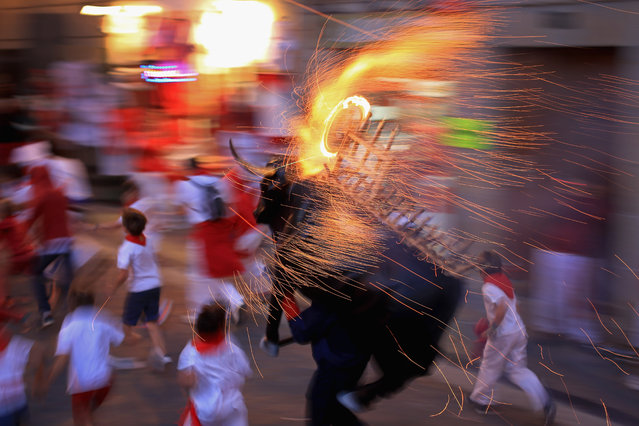 "People and children are chased by a Toro del Fuego (flaming bull) as it is runs through the streets of Pamplona on the third day of the San Fermin Running Of The Bulls Festival  on July 8, 2014 in Pamplona, Spain. The annual Fiesta de San Fermin, made famous by the 1926 novel of US writer Ernest Hemmingway ""The Sun Also Rises"", involves the running of the bulls through the historic heart of Pamplona. (Photo by Christopher Furlong/Getty Images)"