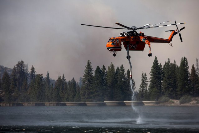 "A firefighting helicopter sucks water out of Hume Lake to battle the so-called ""Rough Fire"" in the Sequoia National Forest, California, August 21, 2015. (Photo by Max Whittaker/Reuters)"